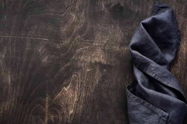 Texture de bois brun foncé avec une serviette ou une serviette de cuisine en coton