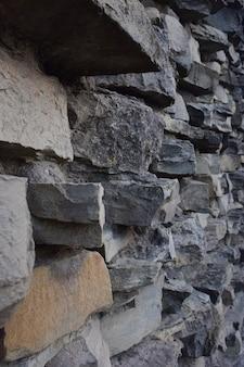 Texture bordée de pierre sur le mur, de différentes formes et nuances pour l'ensemble du cadre
