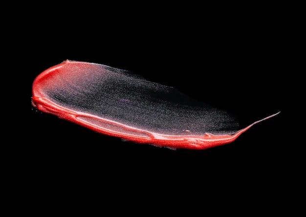 Texture de brillant à lèvres chatoyant rouge taché sur fond noir