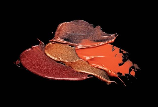 Texture de brillant à lèvres chatoyante orange rouge tachée sur fond noir