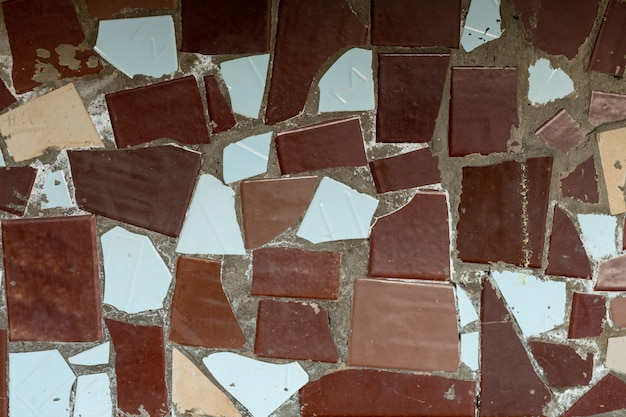 Texture de carreaux cassés multicolores sur un mur de béton