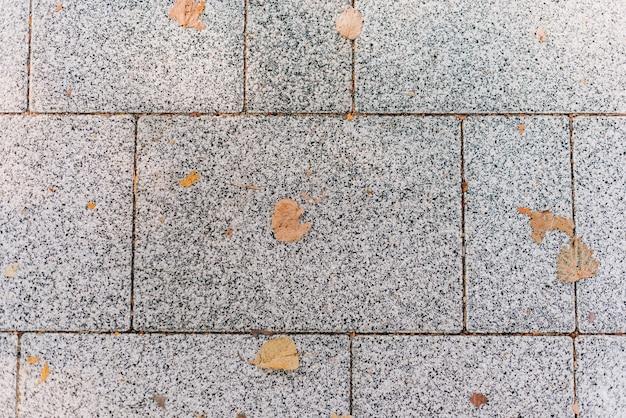 Texture de chaussée en pierre grise. pavés avec des feuilles d'automne jaunes
