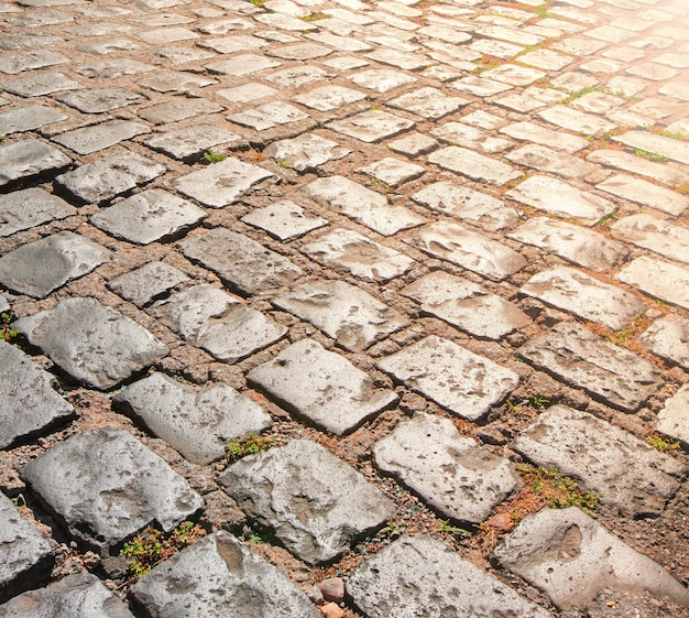 La texture de la chaussée en pierre avec la lumière du soleil