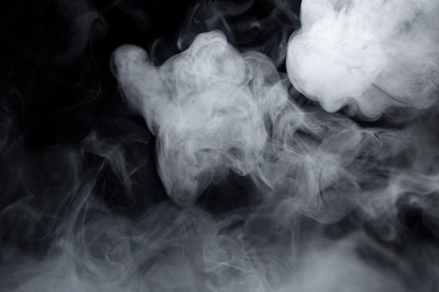 Texture de cigarette blanche fumée sur fond noir