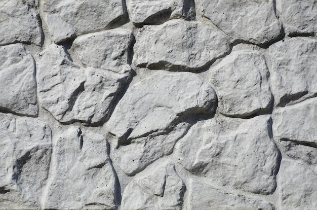 Texture de clôture en béton avec relief et texture comme un mur de pierre