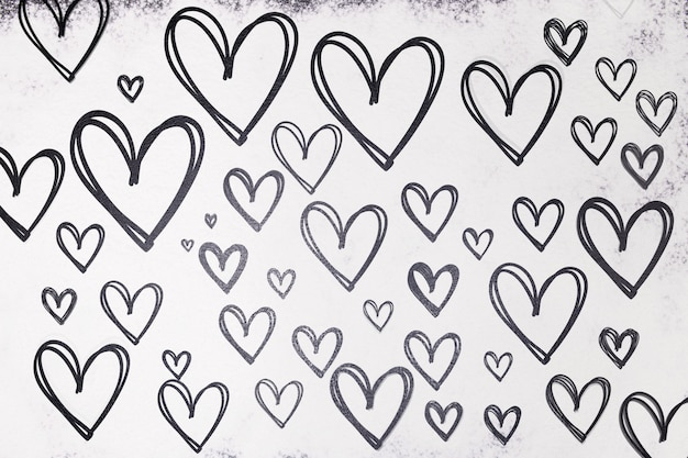 Texture des coeurs dessinés en noir sur fond blanc de farine. la saint-valentin.
