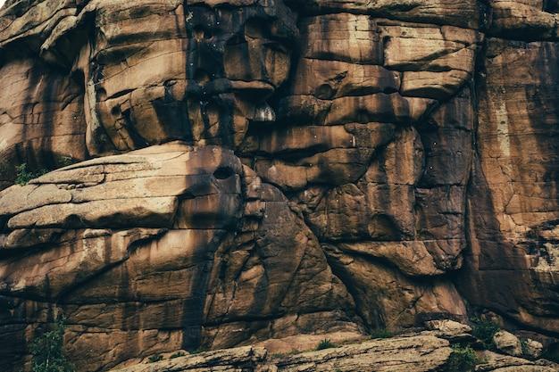 La texture de la colline de roche calcinée est partiellement recouverte de verdure. arrière-plan de rock hill est brûlé dans l'antiquité texture close-up