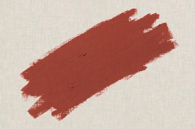 Texture de coup de pinceau de peinture à l'huile brun orangé sur une toile beige texturée