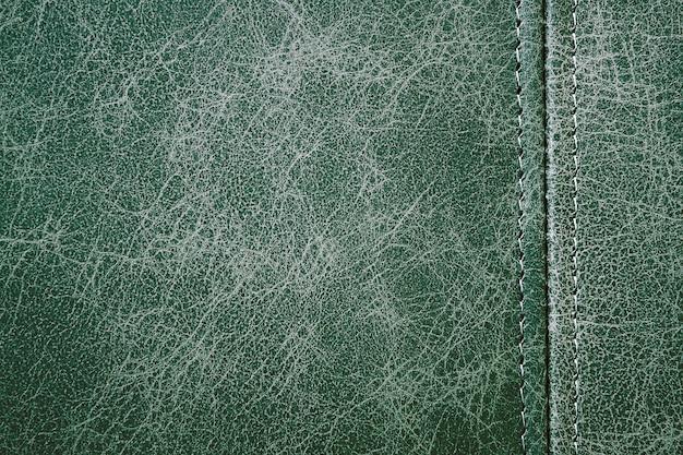 Texture cuir vert avec une couture verticale, fond gros plan