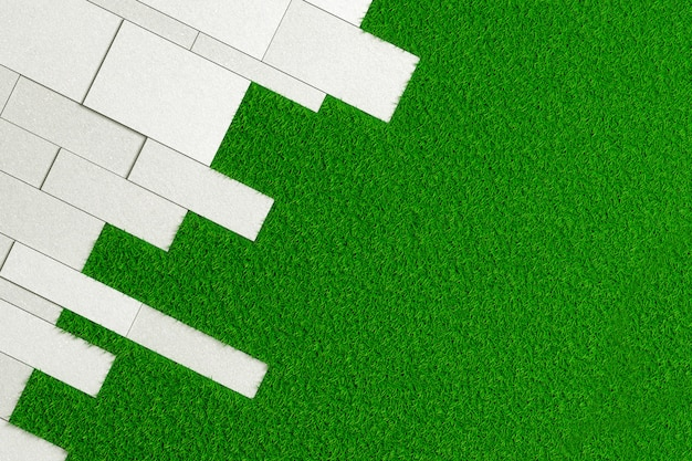 Texture de dalles de différentes tailles de béton brut posé en angle sur une pelouse verte