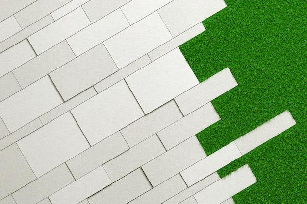 Texture de dalles de différentes tailles de béton brut posées en angle sur une pelouse verte.