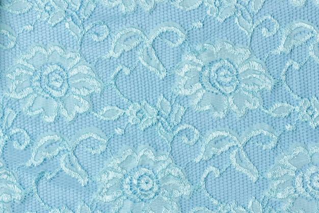 Texture de dentelle bleue avec des fleurs sur fond bleu.