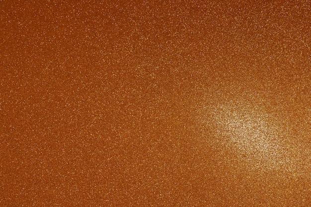 Texture dorée avec des étincelles et une tache de lumière pour le fond.