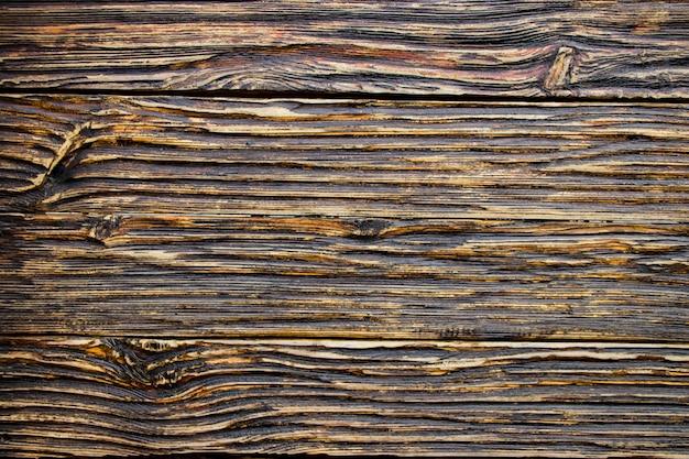 La texture du bois vieilli. les planches sont noires et brunes. bois vieilli artificiellement. texture profonde. le concept d'un vieil arbre.