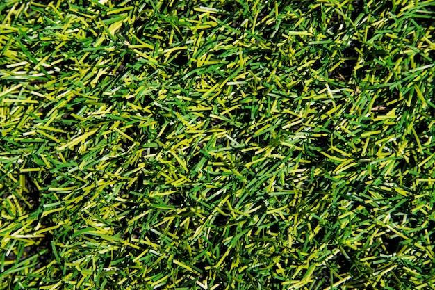 La texture du gazon artificiel vert. revêtement pour stades sportifs et décorations.