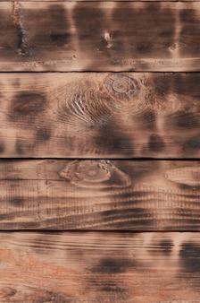 La texture du mur en bois brûlé. mur de longues planches en bois orange lisse avec une texture de friture noire spécifique