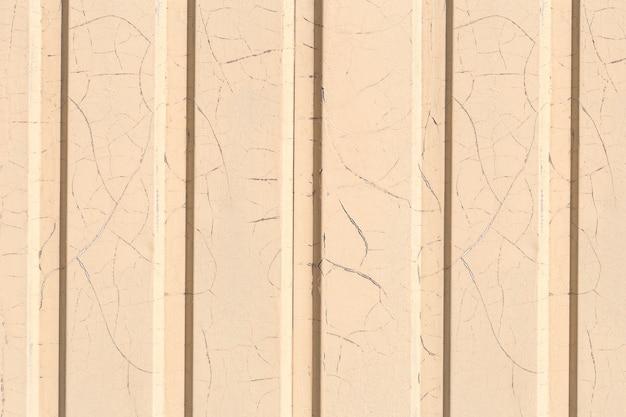 La texture du mur avec des panneaux de parement est peinte en jaune avec beaucoup de petites fissures du temps.