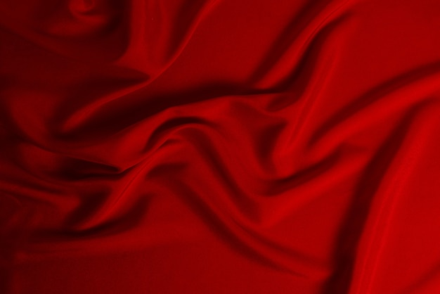 La texture du tissu de luxe en soie rouge ou en satin peut être utilisée comme arrière-plan abstrait. vue de dessus
