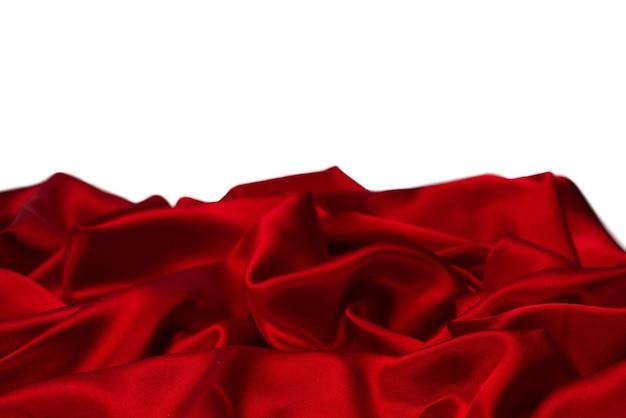 La texture du tissu de luxe en soie rouge ou en satin peut être utilisée comme surface abstraite. isolé sur une surface blanche.