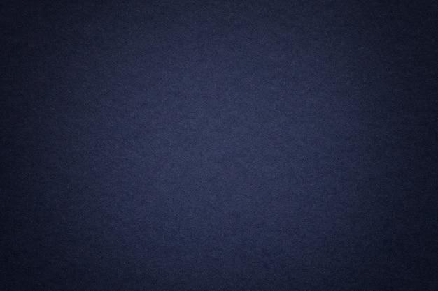 Texture du vieux fond de papier bleu marine, agrandi. structure de carton dense.