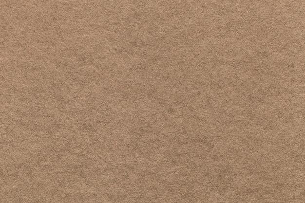 Texture du vieux fond de papier brun clair, agrandi. structure de carton dense