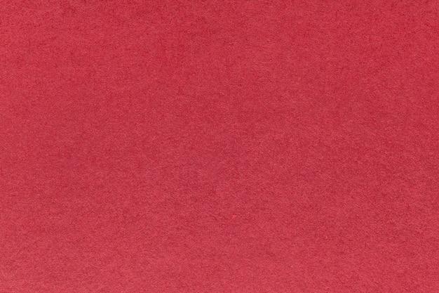 Texture du vieux fond de papier rouge foncé, agrandi. structure en carton à vin dense.