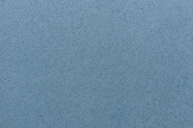 Texture du vieux gros plan de papier bleu clair. structure d'un papier peint en carton dense mat. fond de feutre denim