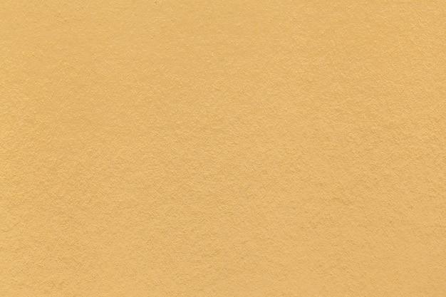 Texture du vieux gros plan de papier jaune clair. structure d'un carton dense. le fond doré
