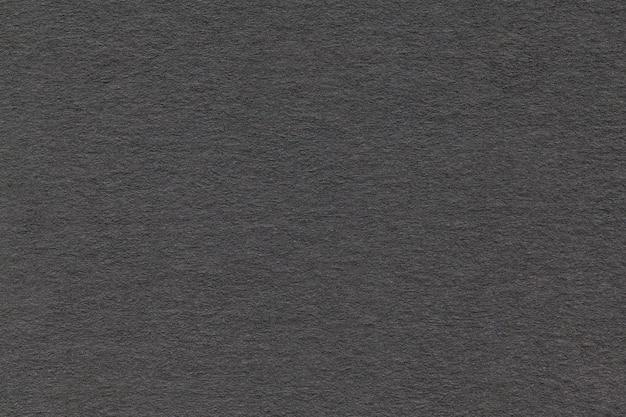 Texture du vieux papier gris closeup. structure d'un carton dense. le fond noir