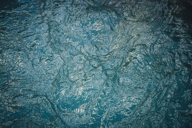 Texture d'eau calme bleu foncé du lac. ondulations méditatives à la surface de l'eau. nature fond minimal de lac vert profond. toile de fond naturelle d'eau turquoise foncée claire. plein cadre de fragment de lac.