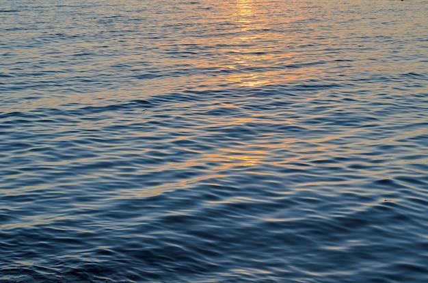 Texture de l'eau de mer aux couleurs du coucher du soleil, bleu et orange du chemin du soleil