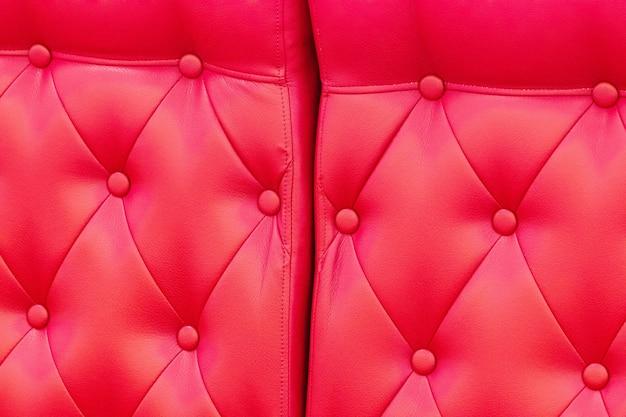 Texture élégante en cuir rouge brillant saturé de chaise de canapé.
