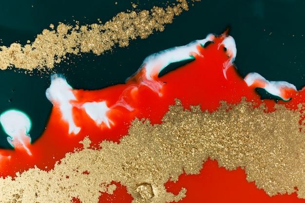 Texture d'encre mélangée rouge, verte et or