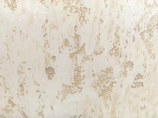 Texture enduit beige décoratif imitant le vieux mur écaillé.