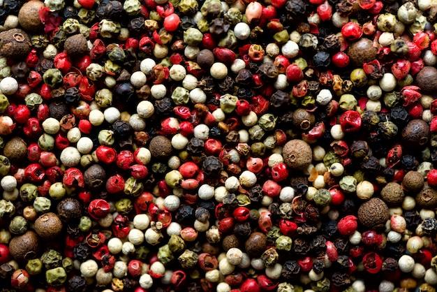 Texture d'épices au poivre. grains de poivre multicolores, mélange de grains colorés. ingrédients pour la cuisine, vue de dessus