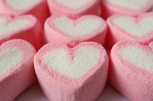 Texture fermée de bonbons à la guimauve en forme de cœur rose et blanc pastel