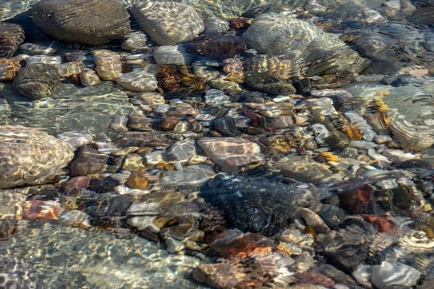 Texture de fond abstrait, pierres de mer colorées dans l'eau, vue de dessus
