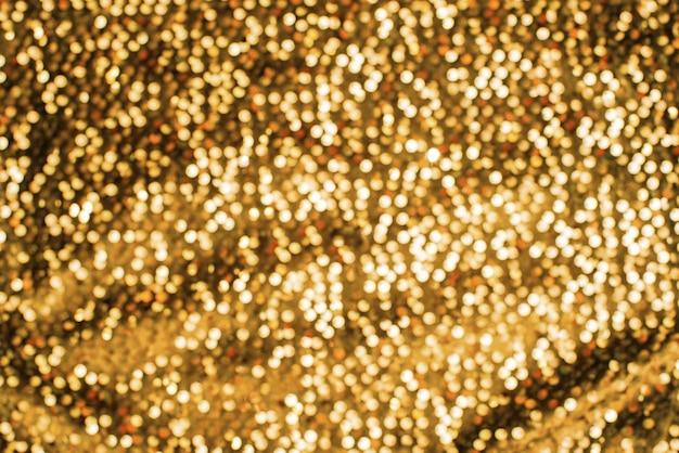 Texture de fond festive scintillante de défocalisation de couleur or brillant
