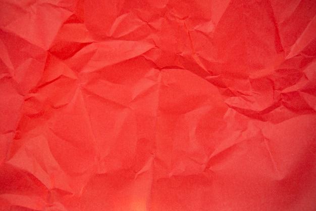 Texture de fond d'une feuille de papier froissé rouge.