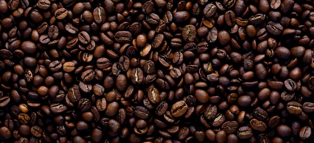 Texture de fond d'un grand nombre de grains de café torréfiés bruns parfumés et frais. une des étapes de la fabrication du café naturel