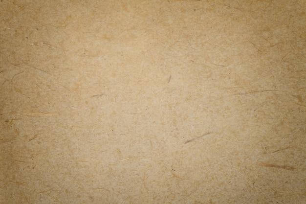 Texture de fond de papier brun foncé vintage avec vignette. structure en carton kraft beige dense avec cadre. gros plan de toile de fond dégradé en feutre.
