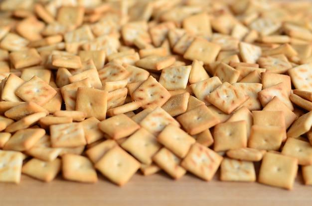Texture de fond de petits carrés comestibles cuits de la pâte et saupoudrés de sel. beaucoup de biscuit salé