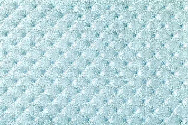 Texture de fond de tissu en cuir bleu clair avec style capitonner. textile denim de style chesterfield.