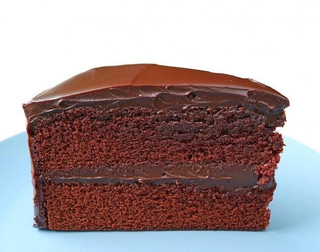 Texture de gâteau au chocolat servi sur une assiette bleue isolée sur fond blanc