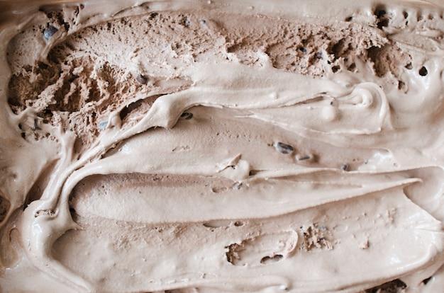 Texture de la glace au chocolat fondante. fond marron.