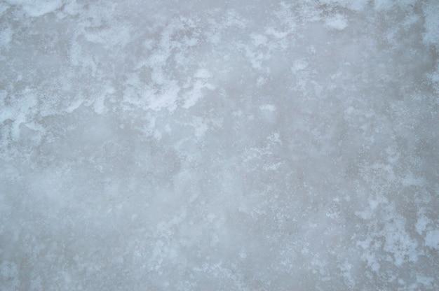 Texture de la glace bleue et grise, fond de glace naturelle avec le givre et la neige