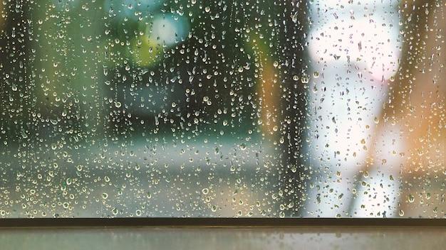 Texture de gouttes de pluie sur le cadre de la fenêtre en verre de la salle de café et de la nature