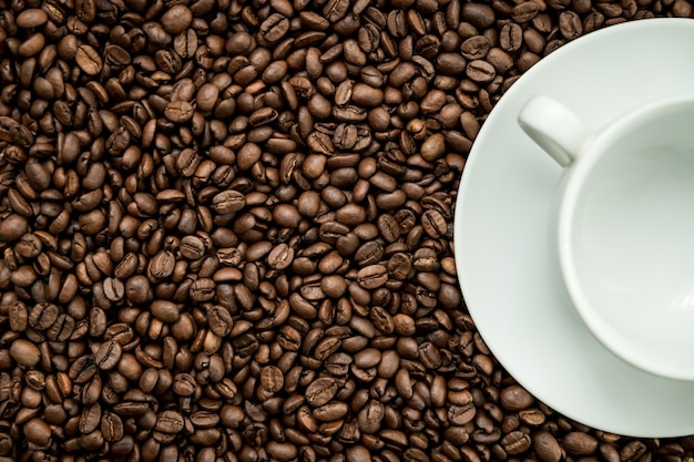 Texture de grains de café avec une tasse blanche