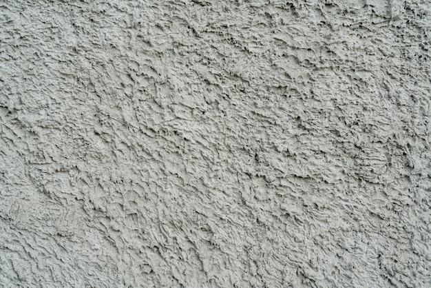 Texture grise de plâtre inégal sur le mur de la maison.