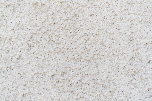 Texture grise de plâtre inégal sur le mur de la maison,